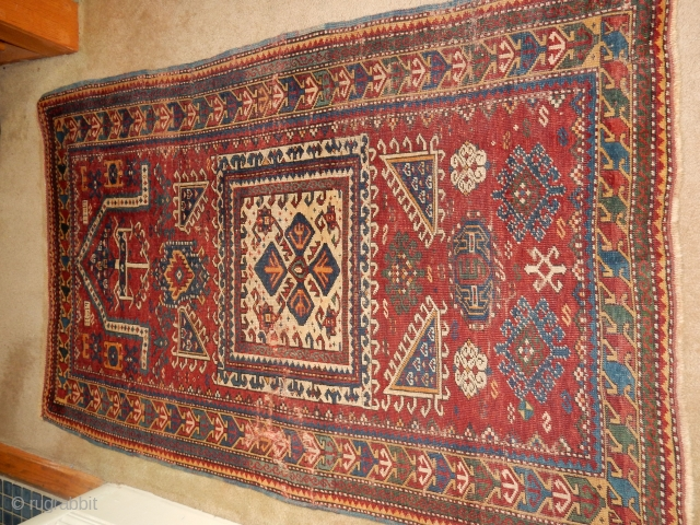 KAZAK OR KUBA RUG WITH BLUE SIDES , THIN RED WEFTS , AND BRAIDED ENDS ...DATED 1898