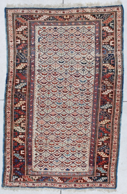 """#6160 Kuba  This circa 1880 Kuba measures 3'5"""" X 5'4"""". It has a lattice design containing different colored flowers on an ivory field. The border is a very crowded (which is unusual) and  ..."""