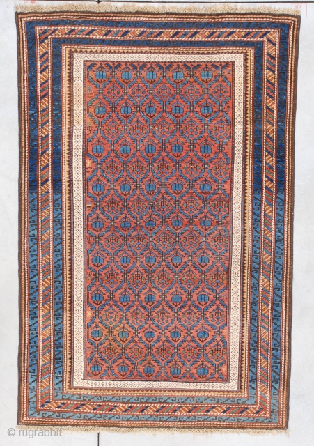 """#7332 Kuba  This last quarter 19th-century Kuba measures 3'8"""" X 5'8"""". It has a rust to terra-cotta colored field with hexagonal repeated compartments ala Marasali Shirvan containing blue flower heads.  The inner  ..."""
