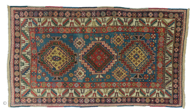 Fabulous antique Kazak rug. Triple medallion on a lovely light blue ground, framed with a very pretty terracotta guard border with rosettes and a geometric cream border. There are some areas of  ...