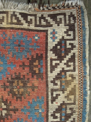 Antique NorthEast Caucasus Avar small rug with 30 four-petal florets in geometric motifs on Red. 32 x 51 inches. In good condition, original side finish, slight residue on verso.