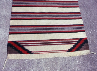 """Navajo rug, 31 X 61"""".  Ca 1940-1950, wool wefts on cotton warps.  Banded design with lightning bolt corners. Very good condition with 3 corner tassels and one stub of the  ..."""