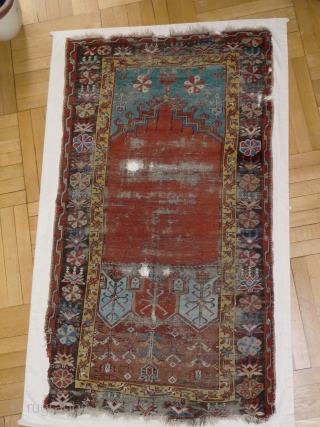 Ladik Prayer rug. Before 1800. 100x200cm, mounted on linen. The great age of this magnificient rug is confirmed, apart from the iconographics, by the colors. The deep stone-red of the 'ocak'( the  ...
