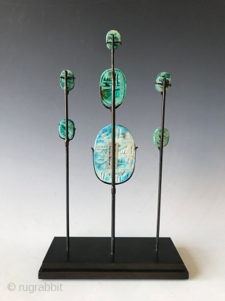 Rare Set of Faience Egyptian Scarab Amulets  Rare faience (blue green glazed) clay Egyptian scarab amulets on a custom stand. Scarabs were popular amulets and impression seals in Ancient Egypt. Egyptian faience is  ...